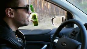 Driver ubriaco, birra bevente dell'uomo mentre guidando, offesa di traffico stock footage