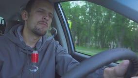 Driver ubriaco l'uomo sta guidando e ballando La fine sul colpo dell'uomo beve la vodka mentre nell'automobile Il pericolo sulla  stock footage