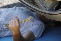 Driver Under A Car. A driver lying under a car with a wrench in his hand, outdoor cropped shot with selective focus Royalty Free Stock Images