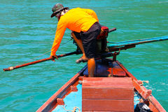 The driver use foot and hand for control the long-tail boat. Royalty Free Stock Images