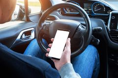 Driver use smart phone in car.  screen for mockup. Modern car interior in background Royalty Free Stock Photo