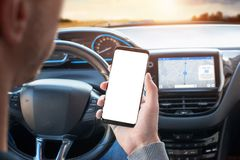 The driver uses the phone while driving. Modern smart phone with round edges. Screen for mockup. Car navigation display in background stock photos