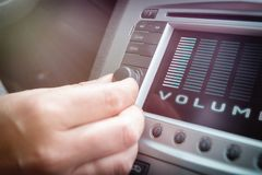 Driver adjusting volume in the car audio system. Driver using knob to adjust volume in the car audio system royalty free stock photography