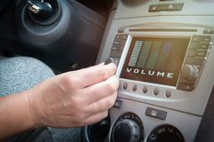 Driver adjusting volume in the car audio system. Driver using knob to adjust volume in the car audio system royalty free stock photo