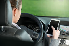 Driver using smartphone and gps navigation in a car. Young female driver using touch screen smartphone and gps navigation in a car Royalty Free Stock Images