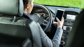 Driver using smartphone and gps navigation in a car Stock Photo