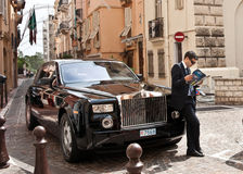 Driver waits by Rolls Royce, Monaco. Stock Images