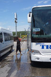 Driver washes bus at rest stop Royalty Free Stock Image