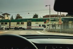 Driver watches the passage of a train behind the gates of a rail Royalty Free Stock Photo