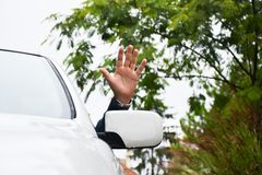Driver waves from a car window Royalty Free Stock Image