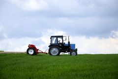 Driver wheeled tractor fertilizing winter wheat with mineral fertilizers royalty free stock image