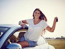 Driver woman showing new car keys. Happy smiling woman is showing keys to her new car, rental car Stock Photo