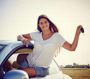 Driver woman showing new car keys. Happy smiling woman is showing keys to her new car, rental car Royalty Free Stock Photo