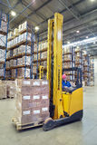 Driver of yellow forklift truck operates, in warehouses. Stock Photo