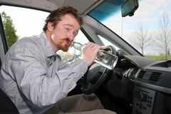 Drivers with a bottle alcohol. Drunk man sitting in drivers with a bottle alcohol Royalty Free Stock Photos