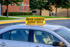 Drivers ed car in high school parking lot. Yellow student driver sign on top of drivers ed car logos removed stock photography