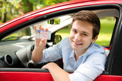Drivers license. Teenager sitting in new car and shows his drivers license