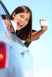 Drivers license car woman. Young woman in car showing blank drivers license or sign out the car window. Happy lovely mixed race Asian Caucasian female model royalty free stock images