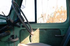 Drivers seat and steering wheel in a rusty old green truck royalty free stock photo
