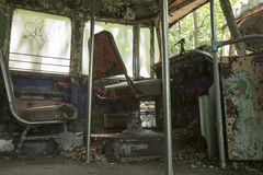 Drivers seats of abandoned trolley car. Chipped and peeling drivers seat and aisle of abandoned trolley car Stock Photos
