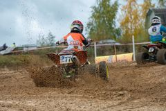 Drives in the mud. SERPUKHOV, RUSSIA - OCTOBER 7, 2017: Abramov Nikolay 77,  Class ATV-JUNIORS, in the 4 stage  MX series, the Red Wings Cup 2017 super country Royalty Free Stock Image