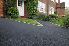 Driveway. New bitumen driveway outside a beautiful brick house in London. Plenty of space for text Stock Photo