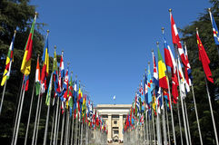Driveway with colorful flags of the UN headquarter. Switzerland, city Geneva, still life of the drive way of the United Nation palace, with the waving flags of Royalty Free Stock Photography