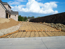 Driveway Construction. New driveway prepared for concrete with rebar, new home in the background Stock Photos
