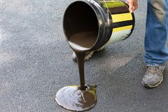 Driveway maintenance, pouring sealant onto asphalt. Do it yourself home maintenance. Driveway resealing repair. Man pours sealant onto asphalt driveway Stock Photography
