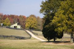 Driveway to Barns. Driveway and fences lead to Horse Barns Royalty Free Stock Photos