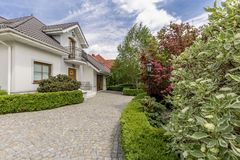 Driveway to mansion with garden. Driveway to a mansion with garden, trees and bushes on sunny day Stock Photos