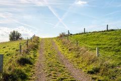 Driveway to the top of a in the Netherlands. Driveway to the top of a Dutch with a fence of gauze and concrete poles on both sides. There are many contrails in royalty free stock photos