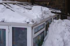 Drivhustak som är skadat av snö som glider av det huvudsakliga taket Royaltyfri Foto