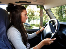 Driving. Young woman driving a car Royalty Free Stock Photos