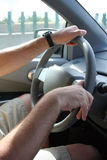 Driving. A man's hands can be seen steering a car while driving royalty free stock photos