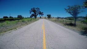 Driving alone Down Rural Road POV. Driving alone down two lane rural road stock footage