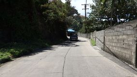 Driving along back street in port elizabeth, bequia. Following a local jitney and a cargo truck on a narrow road in the caribbean stock video footage
