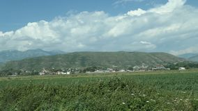 Driving along a field next to Albanian city Finiq in ancient times called Phoinike. Mountains and village in background.  stock footage