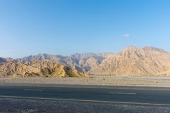 Driving along Jebal Jais Mountain road in Ras al Khaimah, United Arab Emirates UAE as the sun sets against the rocky mountains royalty free stock photo