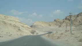 Driving along Jebel Jais mountain road pass by steep sided rock cliffs, around sharp bend, with distant mountain & blue. Driving along Jebel Jais mountain road stock video