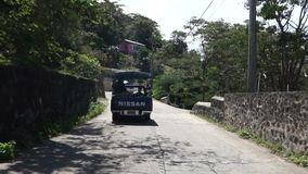 Driving along the main road on bequia in the grenadines. Following a local jitney and a cargo truck on a narrow road in the caribbean stock footage