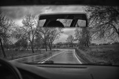Driving along the motorway on a rainy day. Black and white Stock Images