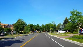 Driving approaching stop sign on residential city road with lush trees during summer day. Driver point of view pov
