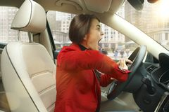 Driving around city. Young attractive woman driving a car Royalty Free Stock Photography