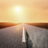 Driving on asphalt road at sunrise towards the sun Stock Photography