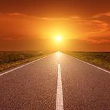 Driving on asphalt road at sunset towards the sun III Stock Photos