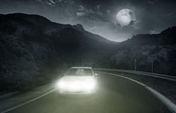 Driving on an asphalt road. Towards the headlights of car at night Stock Images