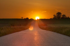 Driving on an asphalt road towards the setting sun Stock Images