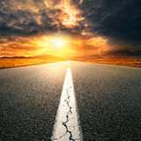 Driving on  asphalt road towards the setting sun Royalty Free Stock Photos