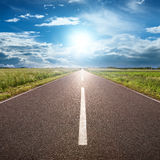 Driving on asphalt road towards the sun Stock Image